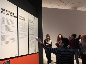 """Brigitte Vogel vom DHM erläutert den Aufbau der Raumtexte in der Sonderausstellung """"1917. Revolution"""" in deutscher, englischer und einfacher Sprache sowie auch Braille und Video in Deutscher Gebärdensprache"""