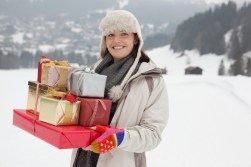Media Bakery ID: CAA0007289 Portrait of smiling woman carrying Christmas gifts in snowy field