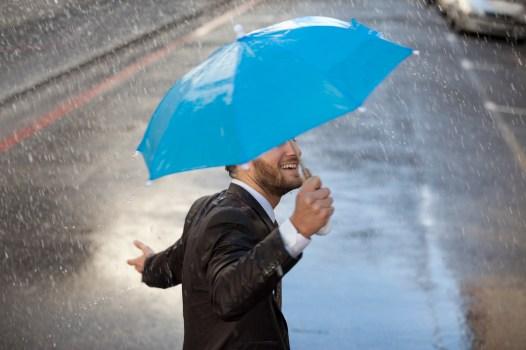 Media Bakrery ID: CAA0007347 Businessman with tiny umbrella walking in rain