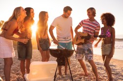 Media Bakery ID: WAV0114256 Group of friends playing guitar on the beach and cooking a barbecue