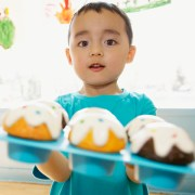 Little boy holding tray of cupcakes --- Image by © Beau Lark/Corbis