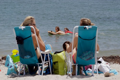 Laura Crovo, second from left, and Meghan Cahill, second from right, ride their paddle-boards as they enjoy a day at the Bill Baggs Cape Florida State Beach in Key Biscayne, Fla., Monday, April 21, 2014. (AP Photo/Alan Diaz)