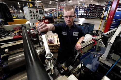 In this May 22, 2013 photo, Kenneth Paull works on a machine at Dokka Fasteners in Auburn Hills, Mich. (AP Photo/Paul Sancya)
