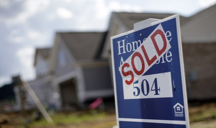 SOLD sticker on a real estate sign in front of a home