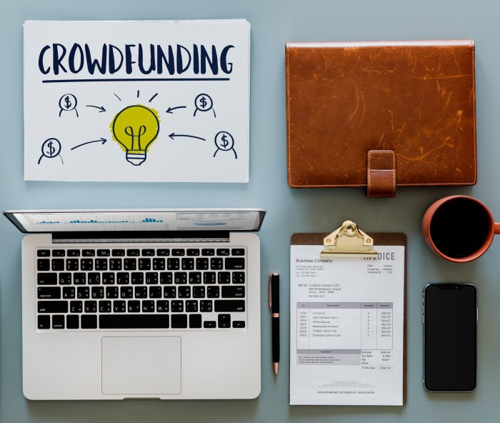Crowdfunding graphic on a tabletop with a laptop, clipboard, other office items