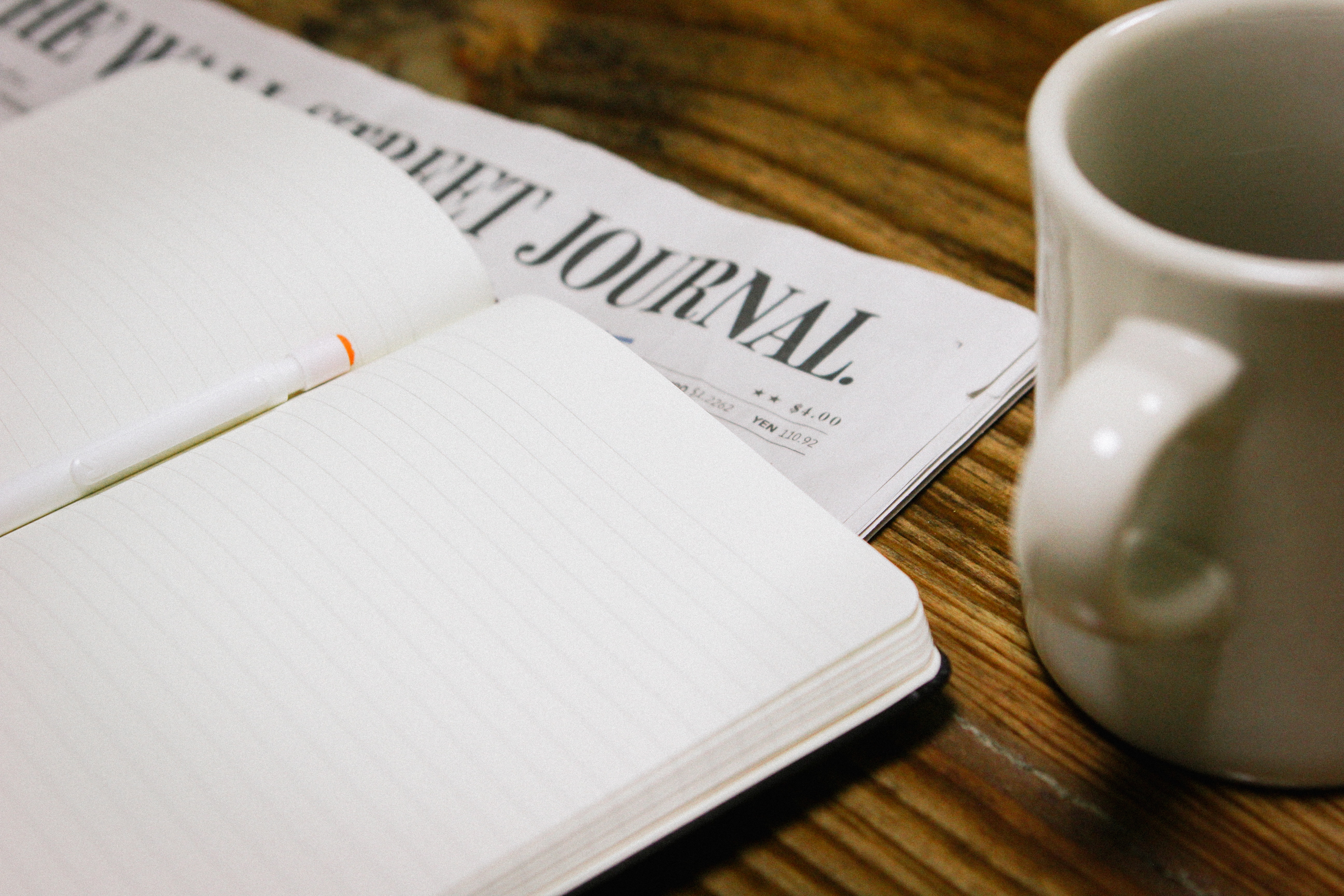 Open notebook with pen laying on top of a copy of the Wall Street Journal, with a white mug to the side.