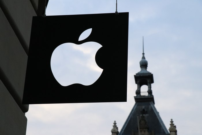 Apple logo sign in front of a building