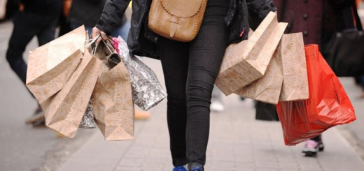 Person walking while carrying multiple shopping bags
