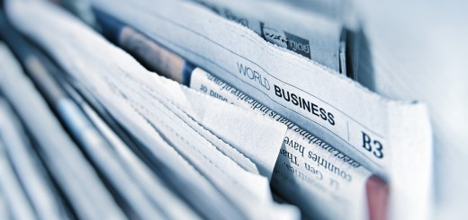 Stack of newspapers with World Business section open