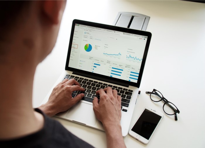 Man sitting in front of an open laptop with charts and graphs on the screen