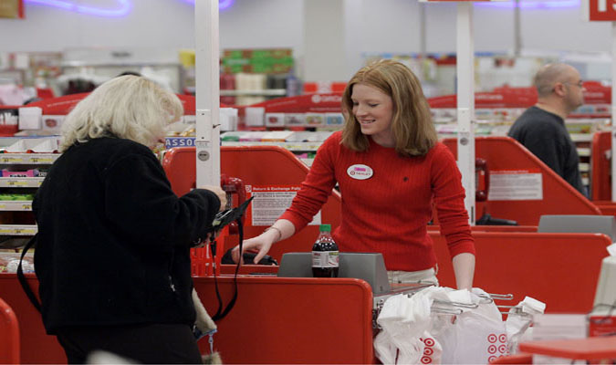 Two women standing at a Target checkout counter, one is an employee