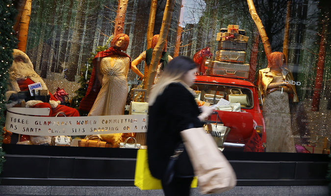 Christmas shopping - a woman walking past a holiday storefront