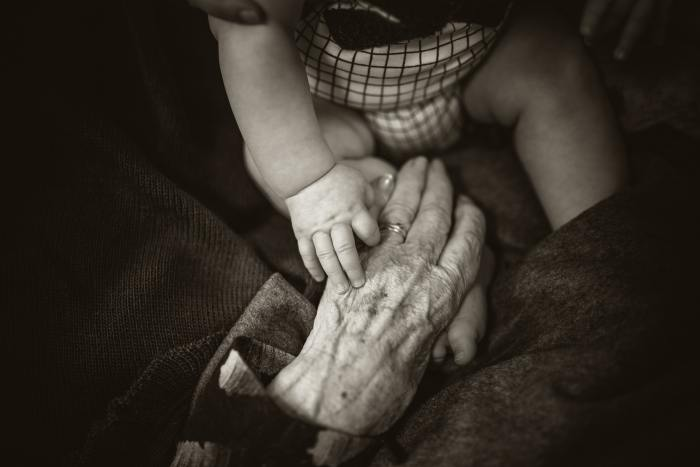 AP Style Reminders - Ages - image of a young child's hand on top of an older person's hand
