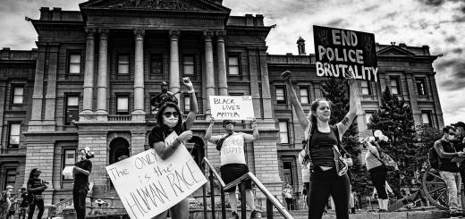 Black and white photo of protesters on steps in front of a building