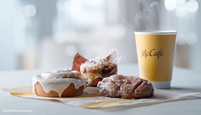 On a table: McDonald's cinnamon rolls and a McCafe in the background