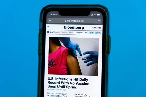 How COVID-19 Impacted the Media: Smartphone displaying a Bloomberg news story about COVID-19 infections