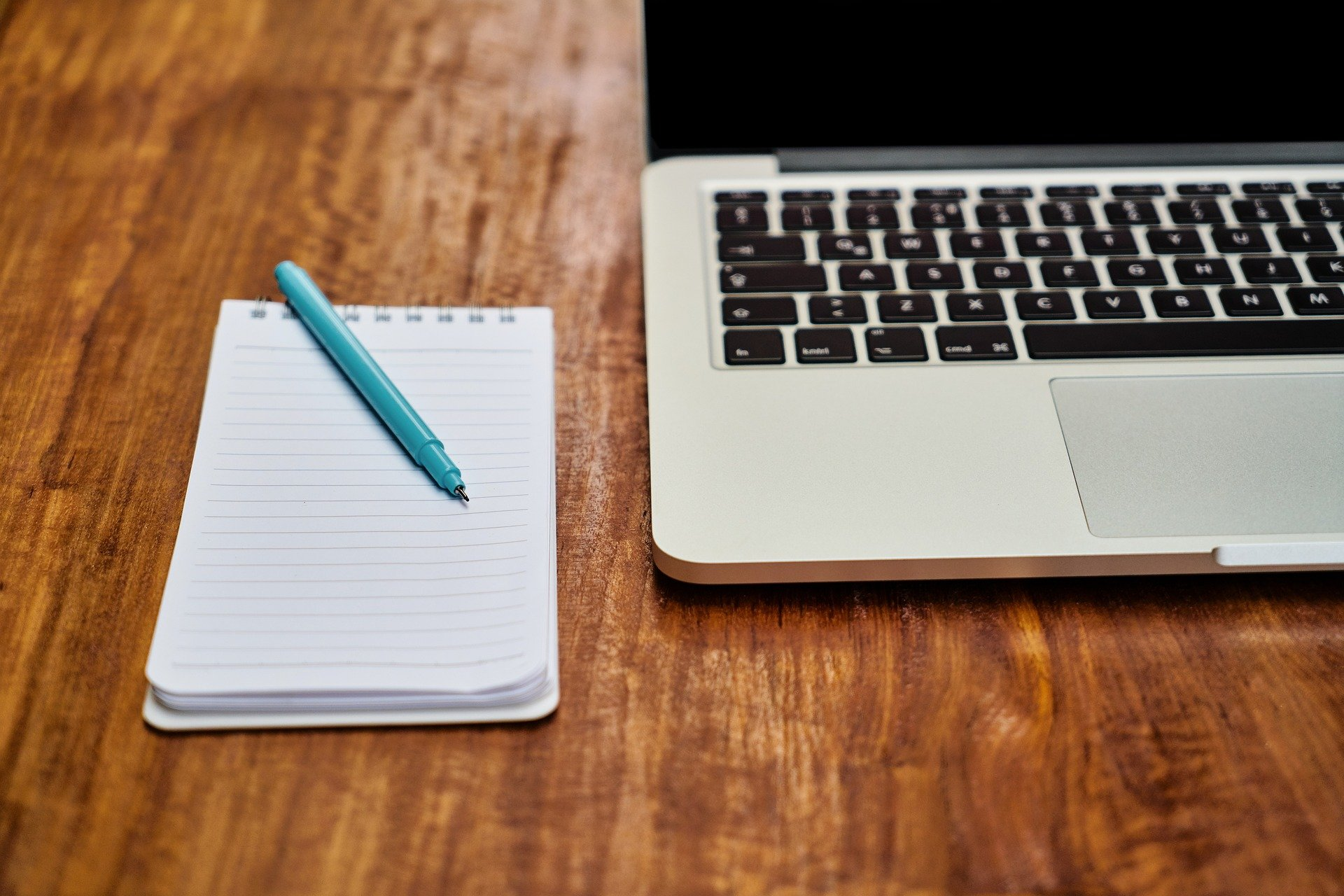 Photo of a notepad and pen next to an open laptop