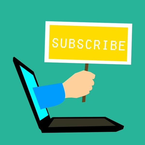 "Graphic of a hand reaching out of a laptop screen holding a ""subscribe"" sign"