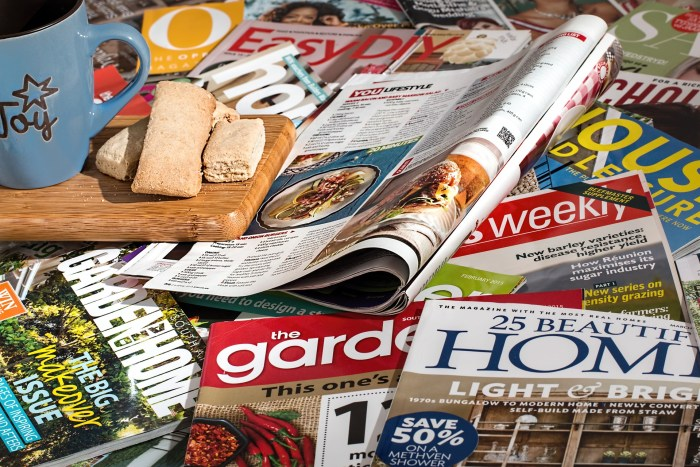 Multiple consumer magazines scattered across a tabletop. Small board with a coffee mug and bread on top of the magazines.