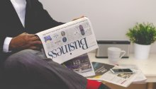 Photo of a person reading the Business section of a newspaper