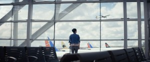Woman in an airport boarding area watching planes take off