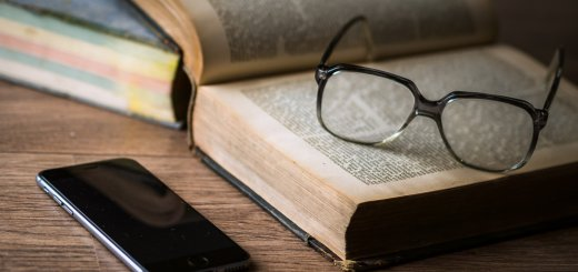 photo of a pair of glasses on top of an open book, with a smartphone nearby
