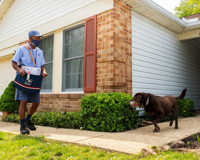 Photo of a U.S. Postal Service worker and a dog