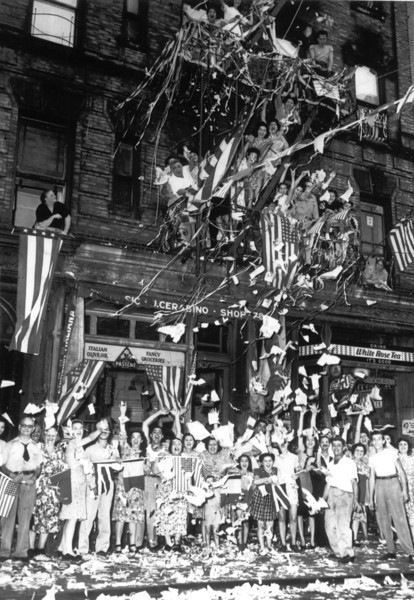 Description of  August 14, 1945: A jubilant crowd of American Italians are seen as they wave flags and toss papers in the air while celebrating Japan's unconditional surrender in their neighborhood in New York City. (AP Photo)