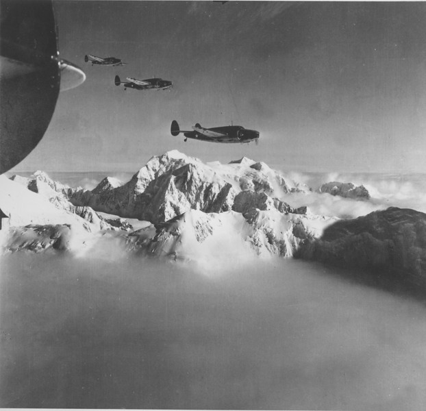 Description of  November 5, 1942: With the towering 20,300 feet peak of Mt. McKinley as a backdrop, a formation of U.S. Army Air Force A-29 planes drone along on the alert in defense in Alaska during World War II. (AP Photo)