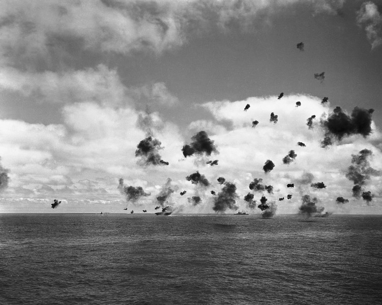Description of  June 4, 1942: The U.S. aircraft carrier Yorktown, left, and the other fighting ships of a United States task force in the Pacific, throw up an umbrella of anti-aircraft fire to beat off a squadron of Japanese torpedo planes attacking the carrier during the battle of Midway. (AP Photo)