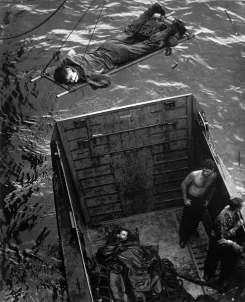 Description of  November 1943: A U.S. soldier wounded in the initial invasion at Empress Augusta Bay is being hoisted aboard a Coast Guard-manned transport off shore of Bougainville island. (AP Photo)