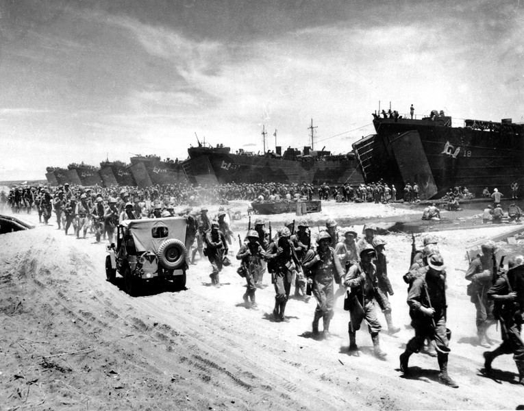 Description of  Dec. 26, 1943: U.S. Marines march ashore as they arrive in six landing crafts at Cape Gloucester on the northwestern coast of New Britain Island, New Guinea. The Allied forces made a second big invasion operation of the Japanese occupied island in an attempt to capture the big air base of Rabual, on the southwestern coast of the island.  (AP Photo/U.S. Coast Guard)