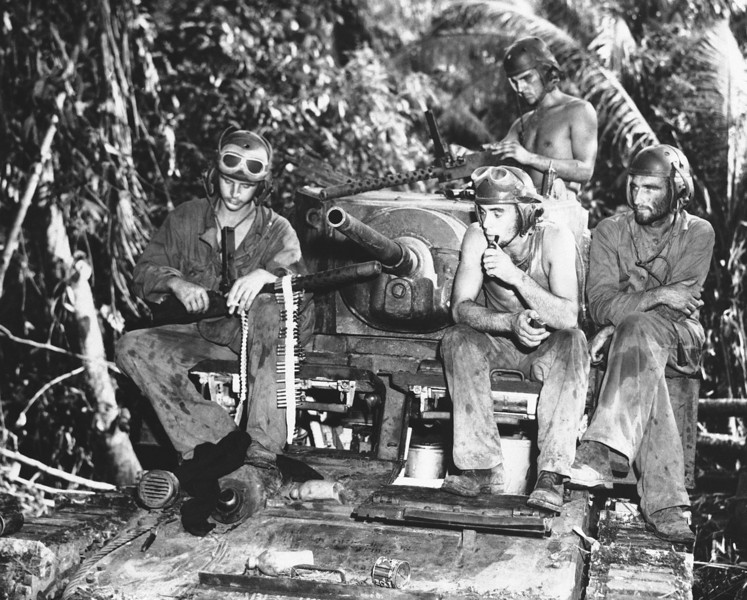 Description of  Sept. 11, 1943: After three days of fighting on the front lines on Munda, a Marine's tank crew take a rest, during which their machine guns are overhauled. This platoon wiped out 30 Japanese pill boxes. Left to right are: Pfc. Arnold McKenzie, Los Angeles, Calif.; Joseph Lodico, Sharon, Mass.; Pvt. Noel M. Billups, Columbus Ohio; and Staff Sgt. Douglas Ayres, Los Angeles. (AP Photo)