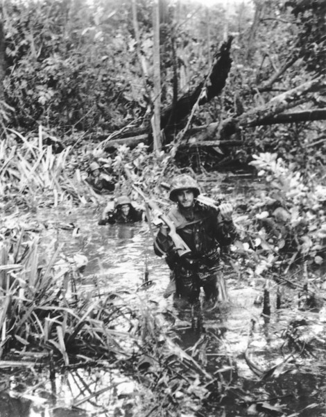Description of  January 1944: U.S. Marines carry their weapons and ammunition overhead as they wade through a wetland area at Cape Gloucester, New Britain Island. (AP Photo)