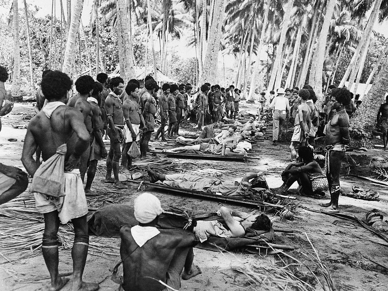 Description of  Jan. 21, 1943: Native stretcher bearers rest in the shade of a coconut grove as they and the wounded American soldiers they are carrying from the front lines at Buna, New Guinea take the opportunity to relax. The wounded are on their way to makeshift hospitals in the rear. (AP Photo)