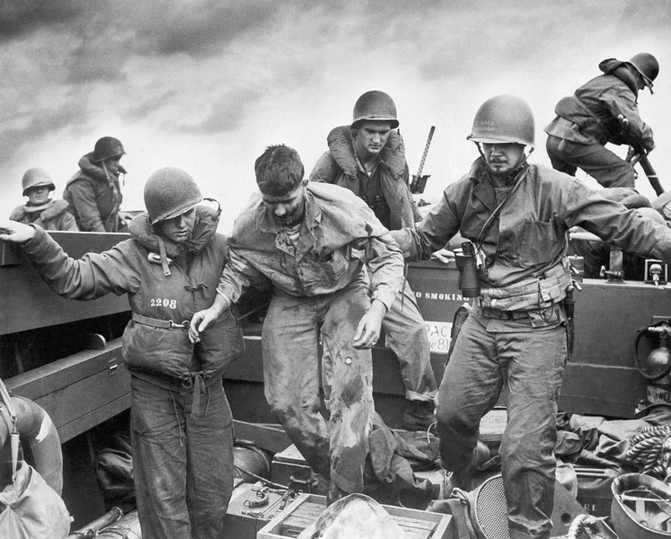 Description of  Feb. 28, 1945: Wounded when Jap fire made a direct hit on an Amtrac, a Marine is transferred by Coast Guardsmen to a landing craft off the flaming shore of Iwo Jima, Japan on D-Day. After darting in with boatloads of Marines, a Coast Guard-manned landing craft ran back to sea with casualties to LST's, specially fitted as temporary hospital ships. Intense enemy fire exacted a heavy toll as the beachhead was established on the island fortress only 750 miles from Tokyo. (AP Photo)