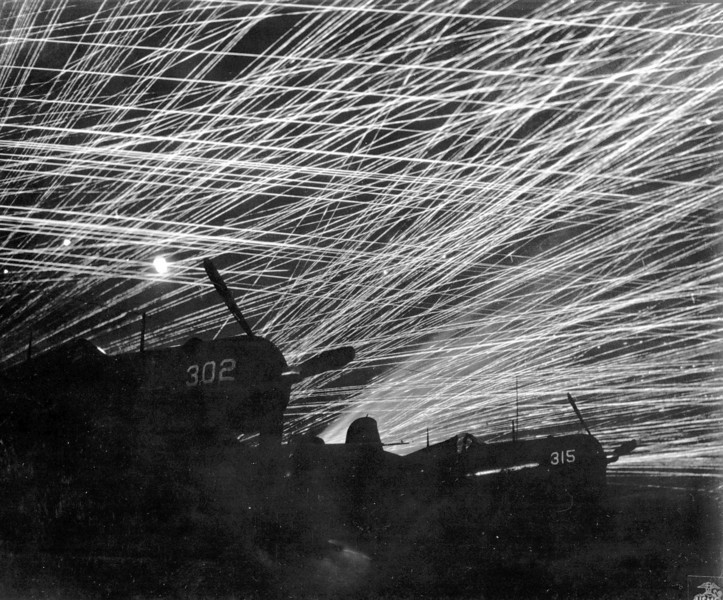 "Description of  March 1945: Japanese night raiders are greeted with a lacework of antiaircraft fire by the U.S. Marine defenders of Yontan airfield, on Okinawa during World War II. In the foreground are Marine Corsair fighter planes of the ""Hells Belles"" squadron standing silhouetted against the sky. (AP Photo)"