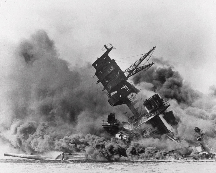 "Description of  December 7, 1941: The battleship USS Arizona belches smoke as it topples over into the sea during a Japanese surprise attack on Pearl Harbor, Hawaii. The ship sank with more than 80 percent of its 1,500-man crew. The attack, which left 2,343 Americans dead and 916 missing, broke the backbone of the U.S. Pacific Fleet and forced  America out of a policy of isolationism. President Franklin D. Roosevelt announced that it was ""a date which will live in infamy"" and Congress declared war on Japan the morning after. (AP Photo)"