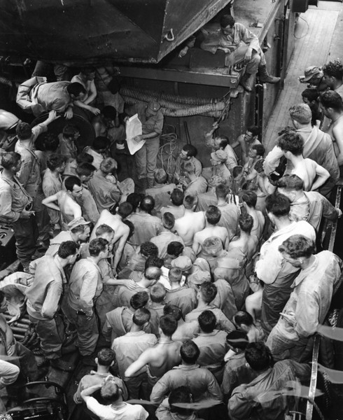 Description of  February 23, 1944: Captain Carter, upper center with map, briefs his men for amphibious assault operations at Arawe, New Britain aboard a troop transport ship. (AP Photo)