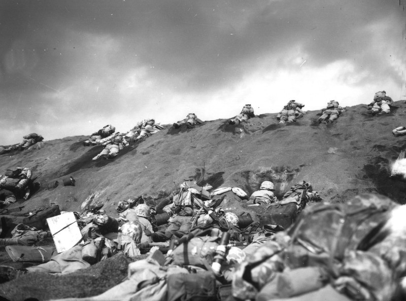 Description of  February, 19, 1945: U.S. Marines of the 5th Divsion inch their way up a sand dune on Red Beach No. 1 toward Mount Suribachi, as the smoke of the battle drifts over them during the initial invasion on Iwo Jima. (AP Photo)