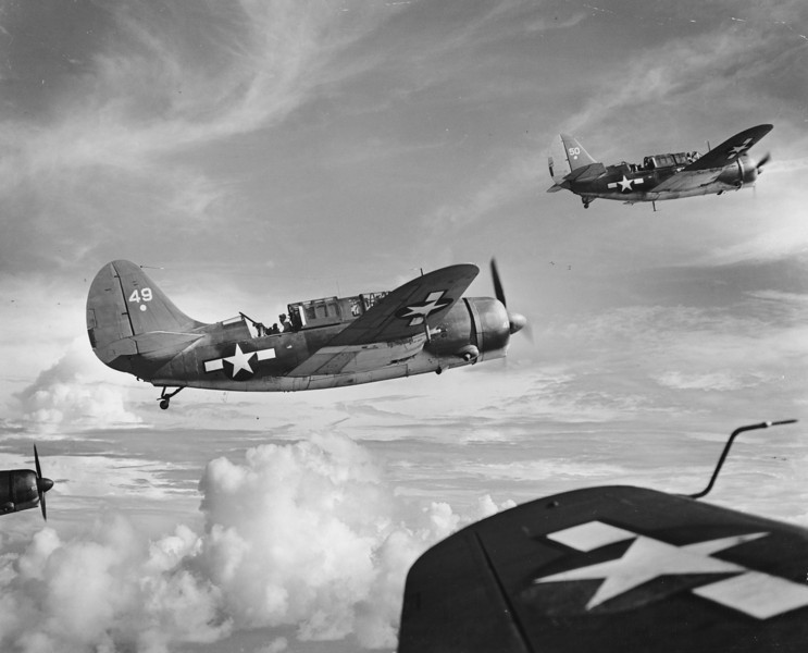 Description of  August 24, 1944: Curtiss Helldivers from the Fast Carrier Task Force 58 are seen midair on a mission over Saipan, in the Mariana Islands. (AP Photo)