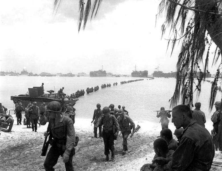 Description of  July 1944: U.S. Army reinforcement troops are seen as they disembark from LST's in the background and proceed across the coral reef toward Saipan beach, Mariana Islands. (AP Photo)