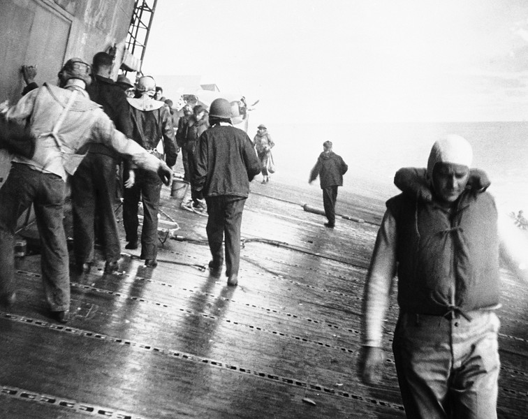 Description of  Sept. 16, 1942: Crewmen picking their way along the sloping flight deck of the aircraft carrier Yorktown as the ship listed, head for damaged sections to see if they can patch up the crippled ship. Later, they had to abandon the carrier and two strikes from a Japanese submarine's torpedoes sent the ship down to the sea floor after the battle of Midway. (AP Photo/U.S. Navy)