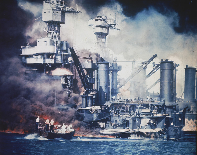 Description of  December 7, 1941: A small boat rescues a USS West Virginia crew member from the water after the Japanese bombing of Pearl Harbor, Hawaii. (AP Photo)