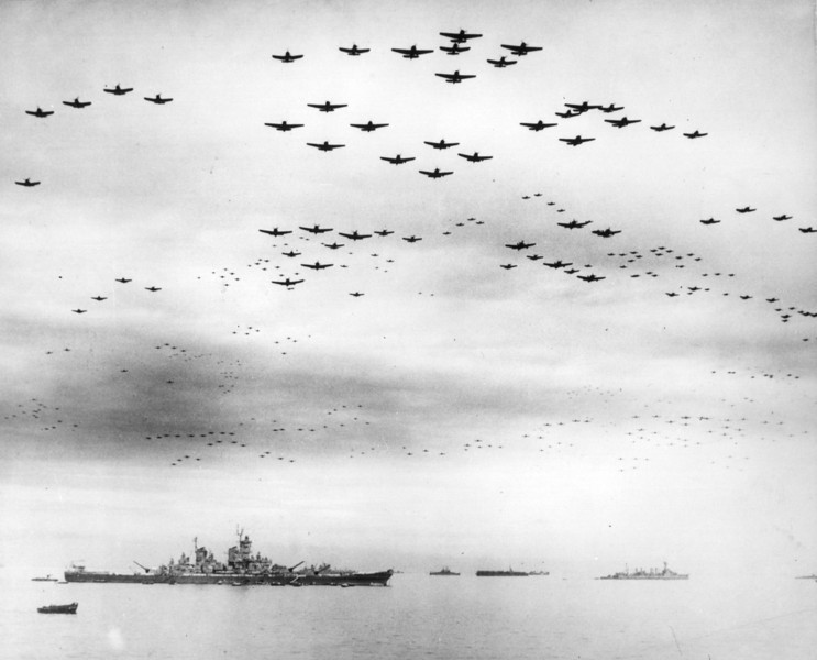 Description of  September 2, 1945: F4U and F6F fighter planes are flying in formation over the USS Missouri, while the surrender ceremonies to end World War II take place aboard the U.S. Navy battleship. (AP Photo)