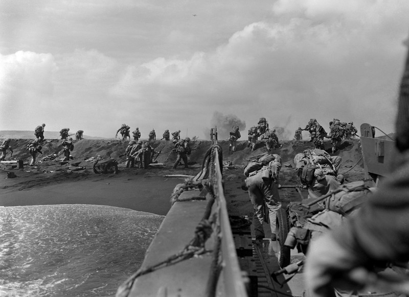 Description of  Feb. 19, 1945: In the Pacific theater of World War II, U.S. Marines hit the beach and charge over a dune on Iwo Jima in the Volcano Islands during the start of one of the deadliest battles of the war against Japan. (AP Photo/Joe Rosenthal)