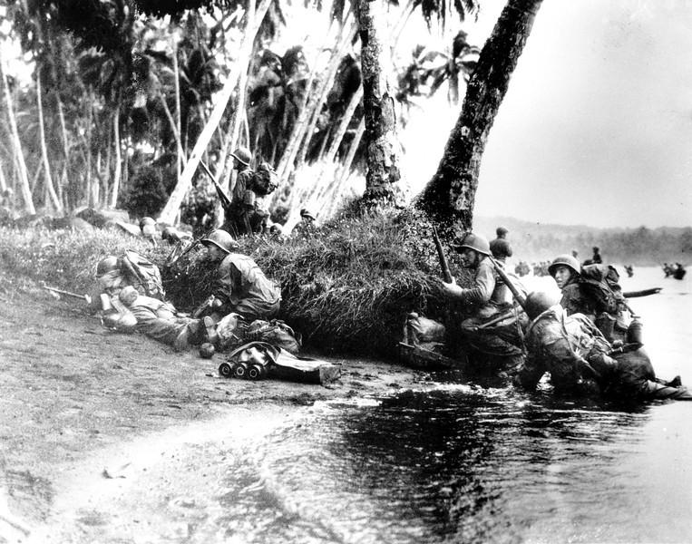 Description of  Aug. 1942: U.S. Marines approach the Japanese occupied Guadalcanal in the Solomon Islands during World War II. (AP Photo)