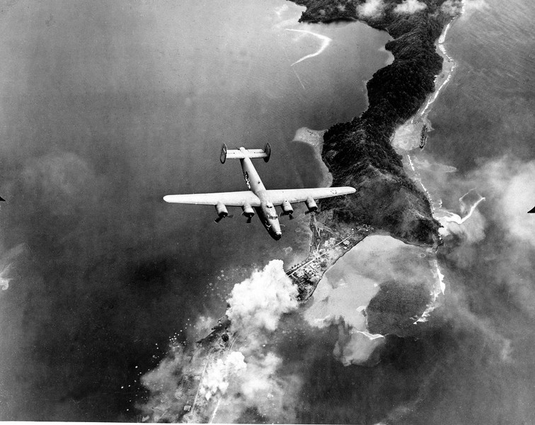 Description of  January 1943: While on a bombing run over Salamau, New Guinea, before its capture by Allied forces, photographer Sgt. John A. Boiteau aboard an army Liberator took this photograph of a B-24 Liberator during World War II. Bomb bursts can be seen below in lower left and a ship at upper right along the beach.  (AP Photo/U.S. Army Force)