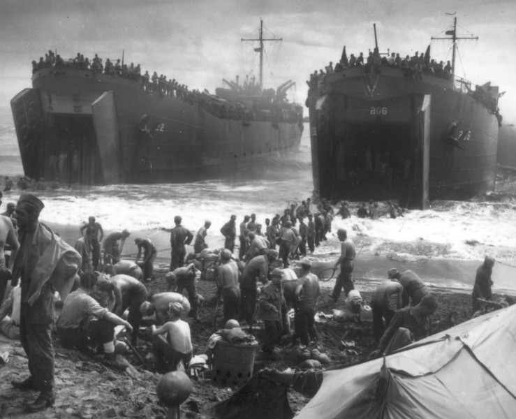 Description of  November 1944: Two Coast Guard-manned landing ships open their jaws as U.S. soldiers line up to build sandbag piers out to the ramps, on Leyte island, Philippines. (AP Photo)