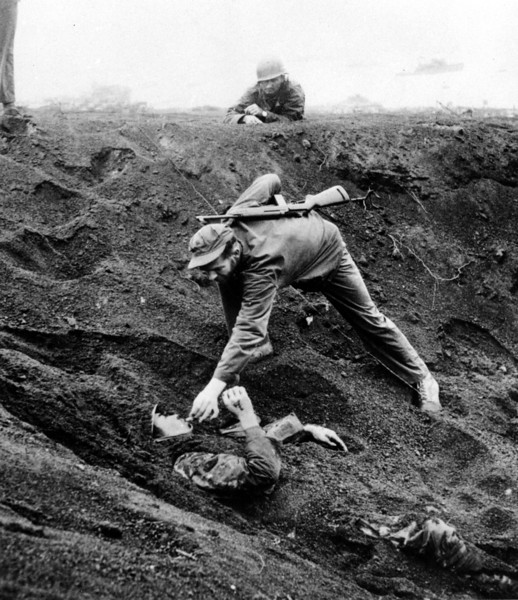 Description of  March 16, 1945: A U.S. Marine approaches a Japanese soldier on Iwo Jima, Japan during World War II. The Japanese soldier was buried for 1 1/2 days in this shell hole playing dead and ready with a live grenade inches away from his hand. The Marines feared he might be further booby trapped underneath his body after knocking the grenade to the bottom of the shell hole. Promising no resistance, the prisoner is given a cigarette he asked for and was dragged free from the hole. (AP Photo)